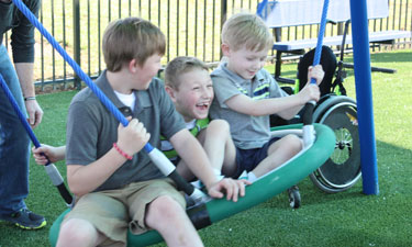 L to R: Brothers Conner, Cayden and Cooper Long enjoy one of the accessible swings at Roll Around the Park.