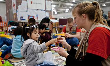 Four-year-old Didi plays with Save the Children staff member Sarah Thompson in the child-friendly shelter space set up at the Atlantic City Convention Center.